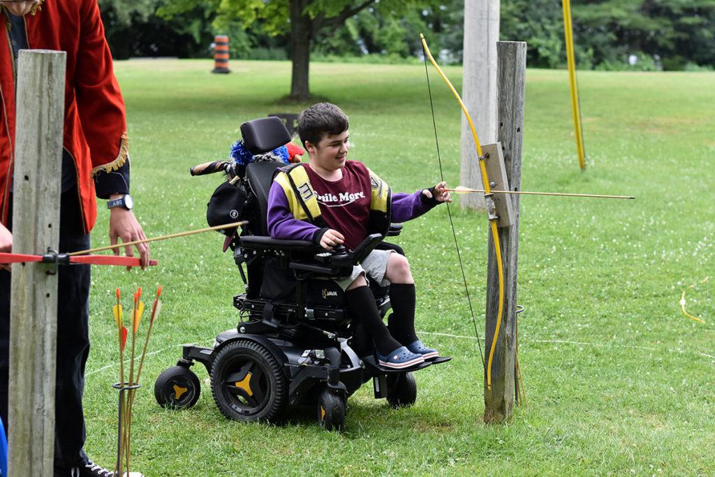 A boy in a power wheelchair pratices archery
