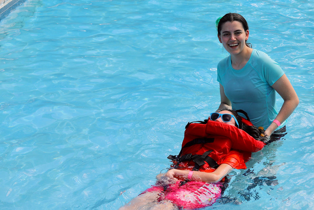A girl swims with the assistance of a camp councilor