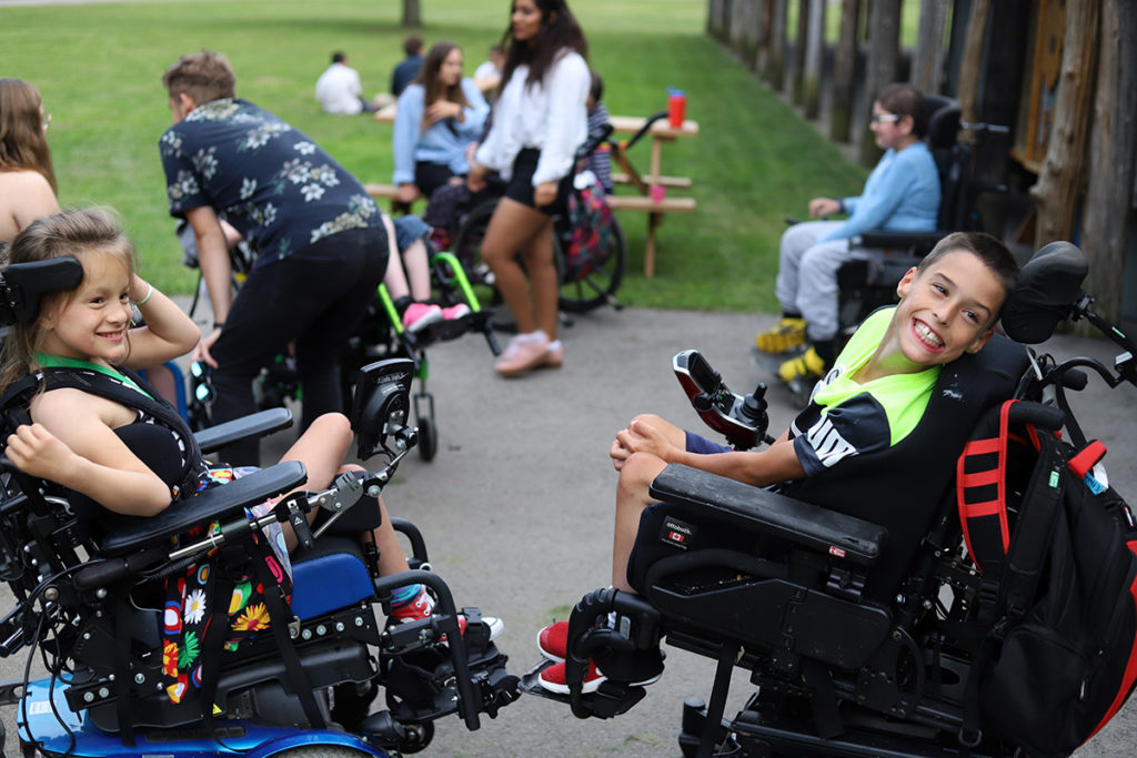 A group of kids in wheelchairs gather outside
