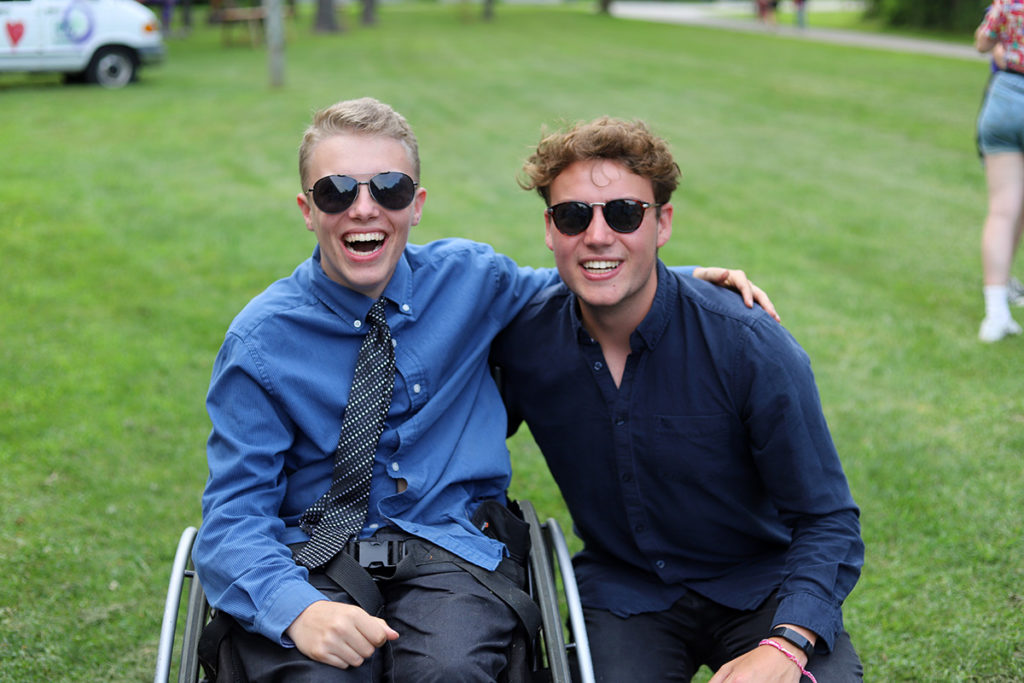 A boy in a wheel chair in a shirt and tie smiles with his arm around a friend